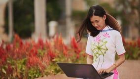 Αρκετά ασιατική συνεδρίαση κοριτσιών με ένα lap-top στο πάρκο στο εθνικό φόρεμα AO Dai με μια ΚΑΠ στο πίσω μέρος μη του Λα απόθεμα βίντεο