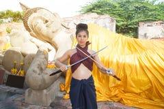 Αρκετά ασιατική τοποθέτηση γυναικών στα ταϊλανδικά αρχαία φορέματα πολεμιστών στοκ εικόνα