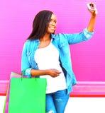 Αρκετά αφρικανική γυναίκα με τις τσάντες αγορών που παίρνουν τη φωτογραφία μόνος-πορτρέτου Στοκ Εικόνες
