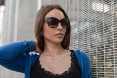 Αρκετά ελκυστική νέα γυναίκα hipster με τα προκλητικά χείλια στα μοντέρνα γυαλιά ηλίου σε ένα μοντέρνο μπλε πλεκτό ακρωτήριο στοκ εικόνα με δικαίωμα ελεύθερης χρήσης