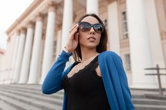Αρκετά ελκυστική νέα γυναίκα hipster με τα προκλητικά χείλια στα μοντέρνα γυαλιά ηλίου σε ένα καθιερώνον τη μόδα μπλε πλεκτό ακρω στοκ φωτογραφία