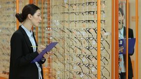 Αρκετά θηλυκός οπτικός που αναθεωρεί τα γυαλιά στην οπτική απόθεμα βίντεο