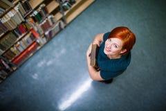 Αρκετά, θηλυκός φοιτητής πανεπιστημίου σε μια βιβλιοθήκη Στοκ Εικόνες