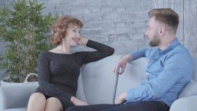 Αρκετά κομψή ώριμη γυναίκα που μιλά με το νεαρό άνδρα στην μπλε συνεδρίαση πουκάμισων στο σπίτι στον καναπέ κοντά επάνω r απόθεμα βίντεο