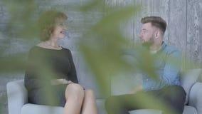 Αρκετά κομψή ώριμη γυναίκα που μιλά με το νεαρό άνδρα στην μπλε συνεδρίαση πουκάμισων στο σπίτι στον καναπέ κοντά επάνω Φύλλα φυτ απόθεμα βίντεο