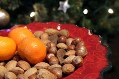 Αρκετά κόκκινο πιάτο Χριστουγέννων με τα παραδοσιακά εορταστικά αμύγδαλα, haz στοκ φωτογραφία με δικαίωμα ελεύθερης χρήσης