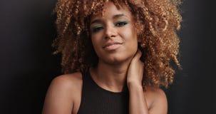 Αρκετά μαύρο κορίτσι με τη μεγάλη τρίχα που θέτει το βίντεο Στοκ φωτογραφία με δικαίωμα ελεύθερης χρήσης