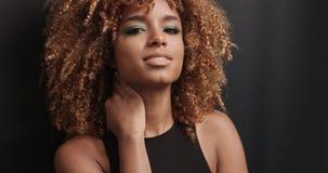 Αρκετά μαύρο κορίτσι με τη μεγάλη τρίχα που θέτει το βίντεο Στοκ Εικόνες