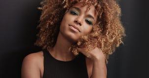 Αρκετά μαύρο κορίτσι με τη μεγάλη τρίχα που θέτει το βίντεο Στοκ Εικόνα