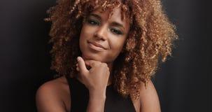 Αρκετά μαύρο κορίτσι με τη μεγάλη τρίχα που θέτει το βίντεο Στοκ Φωτογραφίες