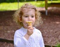 Αρκετά μικρό παιδί, κορίτσι, που τρώει ένα παγωτό Στοκ Εικόνα