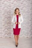Αρκετά μοντέρνη γυναίκα στην πλήρη αύξηση του κόκκινου φορέματος και του άσπρου κοστουμιού στοκ φωτογραφία