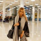 Αρκετά μοντέρνη ελκυστική γυναίκα σε ένα γκρίζο μοντέρνο παλτό με ένα καθιερώνον τη μόδα εκλεκτής ποιότητας μαντίλι με μια μαύρη  στοκ εικόνες