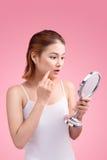 Αρκετά νέα ασιατική γυναίκα που κρατά έναν καθρέφτη, αφή και που ανησυχεί το αβ Στοκ Εικόνα