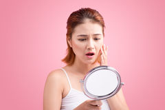 Αρκετά νέα ασιατική γυναίκα που κρατά έναν καθρέφτη, αφή και που ανησυχεί το αβ Στοκ εικόνα με δικαίωμα ελεύθερης χρήσης