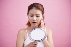 Αρκετά νέα ασιατική γυναίκα που κρατά έναν καθρέφτη, αφή και που ανησυχεί το αβ Στοκ Εικόνες