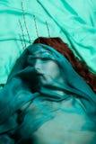 Αρκετά νέα γυναίκα κάτω από το μπλε πέπλο Στοκ Φωτογραφίες