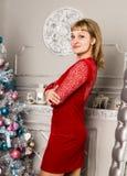 Αρκετά νέα γυναίκα κόκκινο φορεμάτων κοντά στον καθρέφτη τοίχων Στοκ φωτογραφίες με δικαίωμα ελεύθερης χρήσης