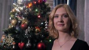 Αρκετά νέα γυναίκα με τα ξανθά μαλλιά κοντά στο χριστουγεννιάτικο δέντρο στο σπίτι απόθεμα βίντεο