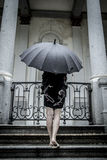 Αρκετά νέα γυναίκα με τη μαύρη ομπρέλα, κάτω από τη βροχή φθινοπώρου σε ένα π στοκ εικόνες