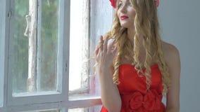 Αρκετά νέα γυναίκα με το στεφάνι των κόκκινων λουλουδιών επάνω φιλμ μικρού μήκους
