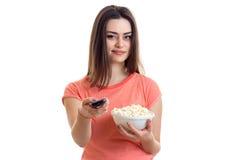 Αρκετά νέα γυναίκα με pop-corn που προσέχει μια TV Στοκ Φωτογραφίες