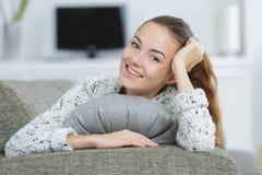 Αρκετά νέα γυναίκα που βρίσκεται στο σπίτι στον καναπέ Στοκ Εικόνες