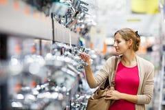 Αρκετά νέα γυναίκα που επιλέγει μια βρύση λουτρών/κουζινών σε μια βασική γούνα Στοκ Εικόνες