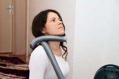 Αρκετά νέα γυναίκα που επισκευάζει την ηλεκτρική σκούπα στο σπίτι Στοκ Εικόνα