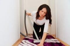 Αρκετά νέα γυναίκα που επισκευάζει την ηλεκτρική σκούπα στο σπίτι Στοκ Φωτογραφία