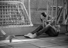 Αρκετά νέα γυναίκα, που κάθεται στο έδαφος που καλύπτει το πρόσωπό της με στοκ φωτογραφία με δικαίωμα ελεύθερης χρήσης