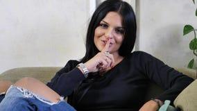 Αρκετά νέα γυναίκα που κάνει το σημάδι παύσης με το δάχτυλο στα χείλια απόθεμα βίντεο