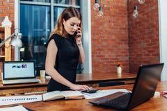 Αρκετά νέα γυναίκα που μιλά στο τηλέφωνο που μετρά χρησιμοποιώντας έναν υπολογιστή που λειτουργεί στο γραφείο που στέκεται στο γρ στοκ φωτογραφίες με δικαίωμα ελεύθερης χρήσης