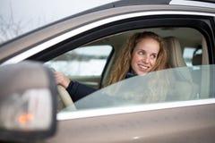 Αρκετά νέα γυναίκα που οδηγεί το νέο αυτοκίνητό της Στοκ Φωτογραφία