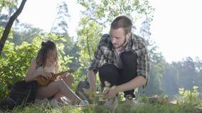 Αρκετά νέα γυναίκα που παίζει ukulele στο υπόβαθρο ενώ ο φίλος της που κάνει την πυρκαγιά στο πρώτο πλάνο στο δάσος απόθεμα βίντεο