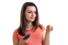 Αρκετά νέα γυναίκα που προσέχει μια TV με pop-corn Στοκ Εικόνες