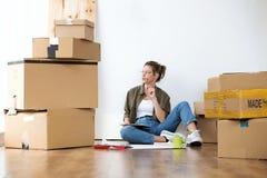 Αρκετά νέα γυναίκα που σκέφτεται για τις ανησυχίες καινούργιου σπιτιού της της καθμένος στο πάτωμα στο σπίτι στοκ εικόνες