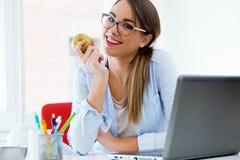Αρκετά νέα γυναίκα που τρώει ένα μήλο στο γραφείο της Στοκ Φωτογραφίες