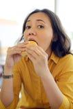 Αρκετά νέα γυναίκα που τρώει Burger στον καφέ Στοκ Εικόνες