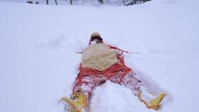 Αρκετά νέα γυναίκα που φορά το αστείο κοστούμι τιγρών που βρίσκεται snowdrift το χειμώνα και που ρίχνει επάνω στο χιόνι κατά τη δ απόθεμα βίντεο