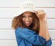 Αρκετά νέα γυναίκα που φορά το θερινά καπέλο και το γέλιο Στοκ Φωτογραφίες
