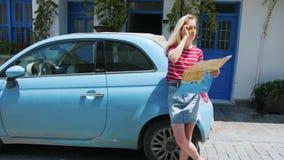 Αρκετά νέα γυναίκα που φορά το πουκάμισο στη μικρή ευρωπαϊκή οδό μπροστά από το μπλε αυτοκίνητο με το χάρτη απόθεμα βίντεο