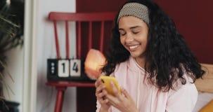 Αρκετά νέα γυναίκα που χαμογελά κουβεντιάζοντας στην κίτρινη συνεδρίαση smartphone στο κρεβάτι στο σπίτι Το κορίτσι στέλνει ένα μ απόθεμα βίντεο