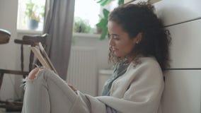 Αρκετά νέα γυναίκα που χρησιμοποιεί την ψηφιακή ταμπλέτα στην άνετη κουζίνα φιλμ μικρού μήκους