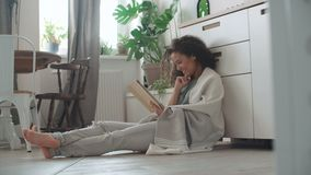 Αρκετά νέα γυναίκα που χρησιμοποιεί την ψηφιακή ταμπλέτα στην άνετη κουζίνα απόθεμα βίντεο