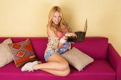 Αρκετά νέα γυναίκα που χρησιμοποιεί το lap-top της χαλαρώνοντας σε έναν καναπέ Στοκ φωτογραφία με δικαίωμα ελεύθερης χρήσης