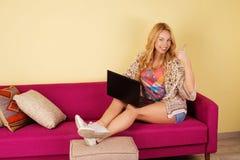 Αρκετά νέα γυναίκα που χρησιμοποιεί το lap-top της χαλαρώνοντας σε έναν καναπέ Στοκ εικόνα με δικαίωμα ελεύθερης χρήσης