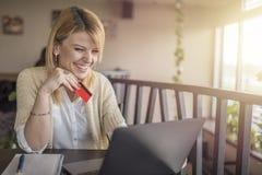 Αρκετά νέα γυναίκα που ψωνίζει on-line χρησιμοποιώντας την πιστωτική κάρτα και την περιτύλιξή της στοκ φωτογραφία