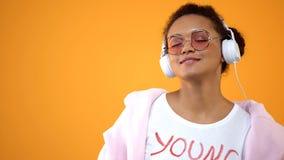 Αρκετά νέα γυναίκα στα άσπρα ακουστικά που απολαμβάνει τον ήχο μουσικής στο κίτρινο υπόβαθρο στοκ εικόνα