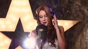 Αρκετά νέα γυναίκα στα ακουστικά που τραγουδούν ένα τραγούδι απόθεμα βίντεο
